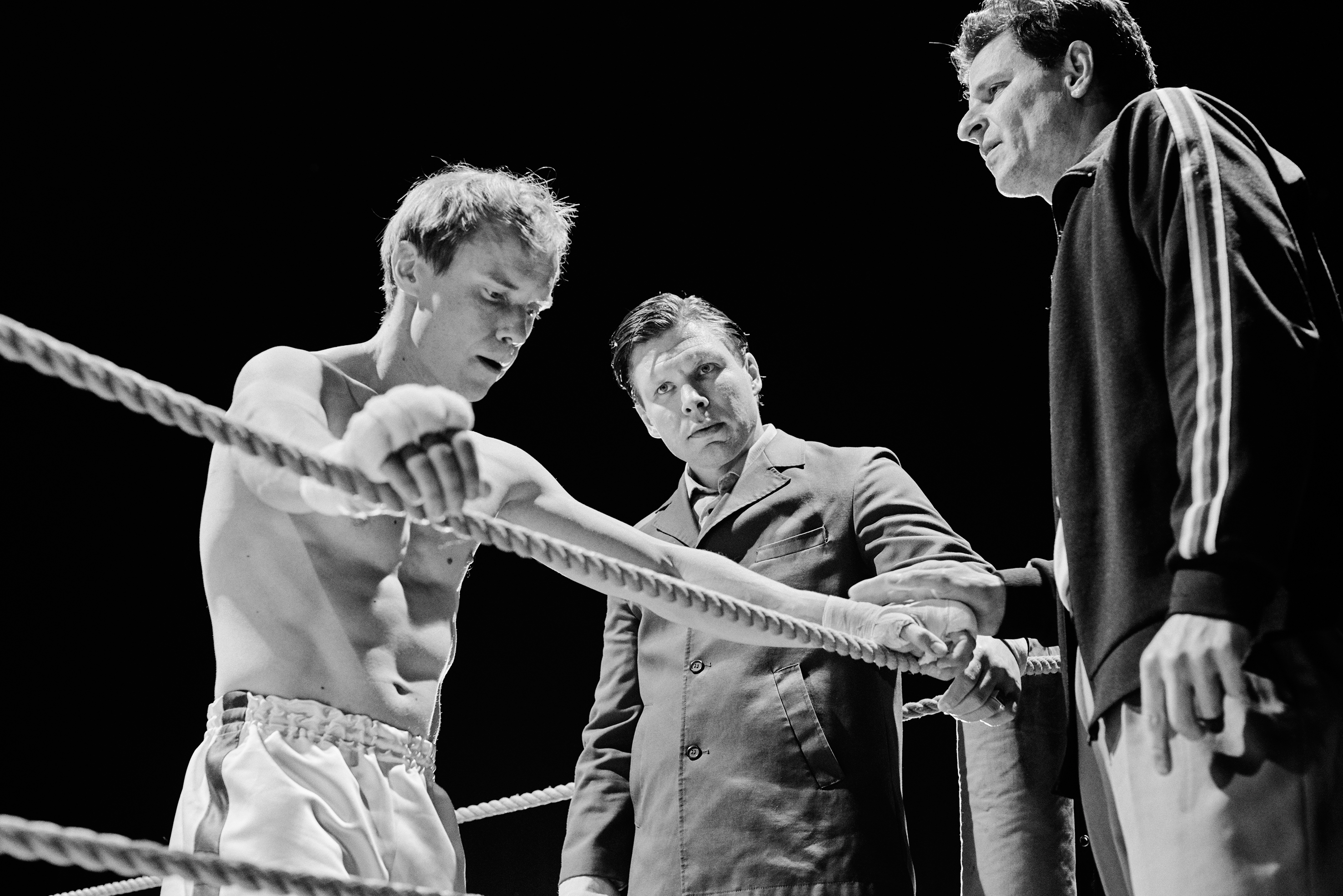 Photograph in black and white, of a boxer holding onto the rope around the boxing ring, thinking. Next to him are two men looking at him.