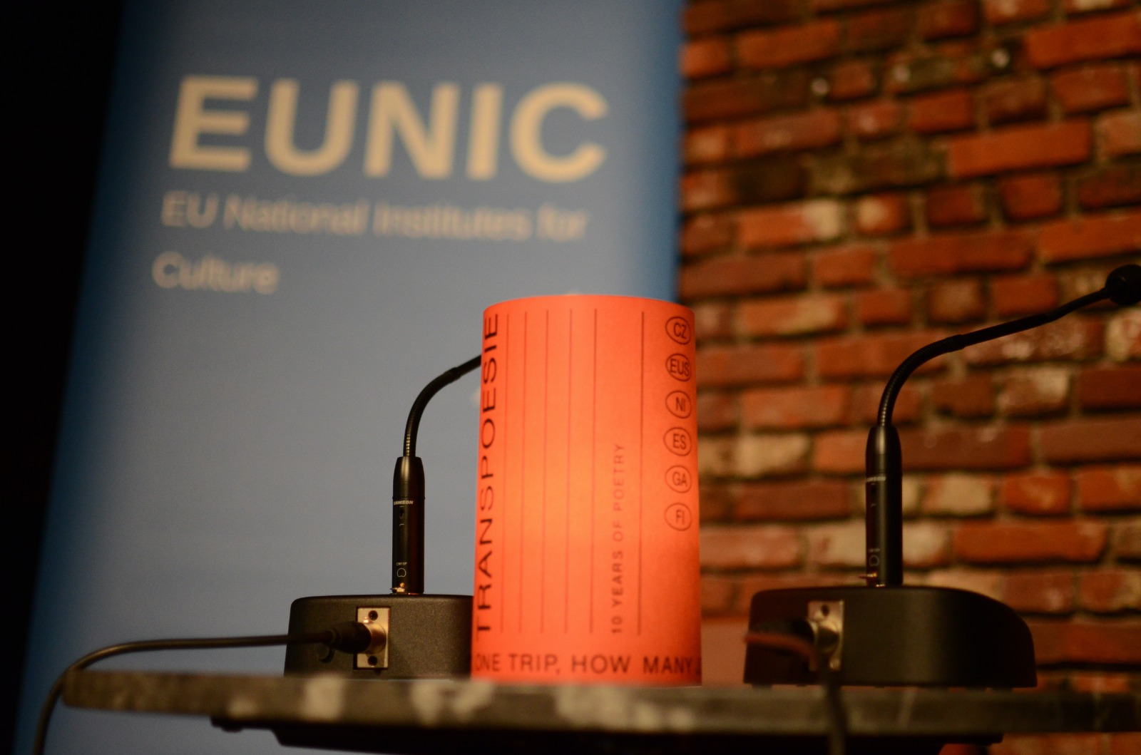 A close-up image of a speaker desk and microphones at a Transpoesie event, with a blue EUNIC banner in the backgournd